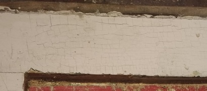 Crackling peeling paint on exterior with signs indicating likely presence of lead.